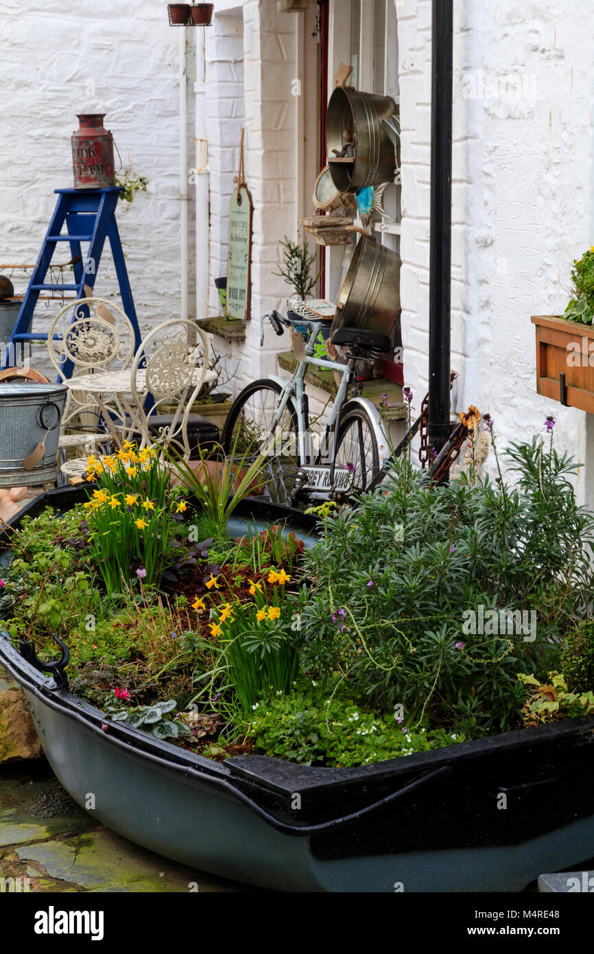 Recycled dinghy planted for winter interest in the tourist fishing village of Polperro, Cornwall, UK - Stock Image