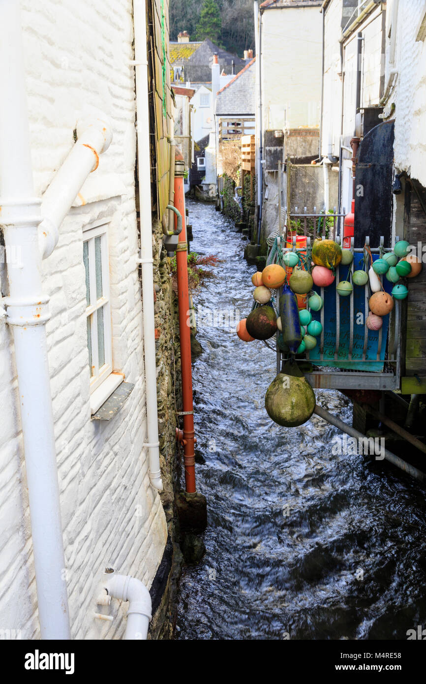 Fast flowing River Pol at Polperro, Cornwall, UK runs between closely positioned old houses - Stock Image