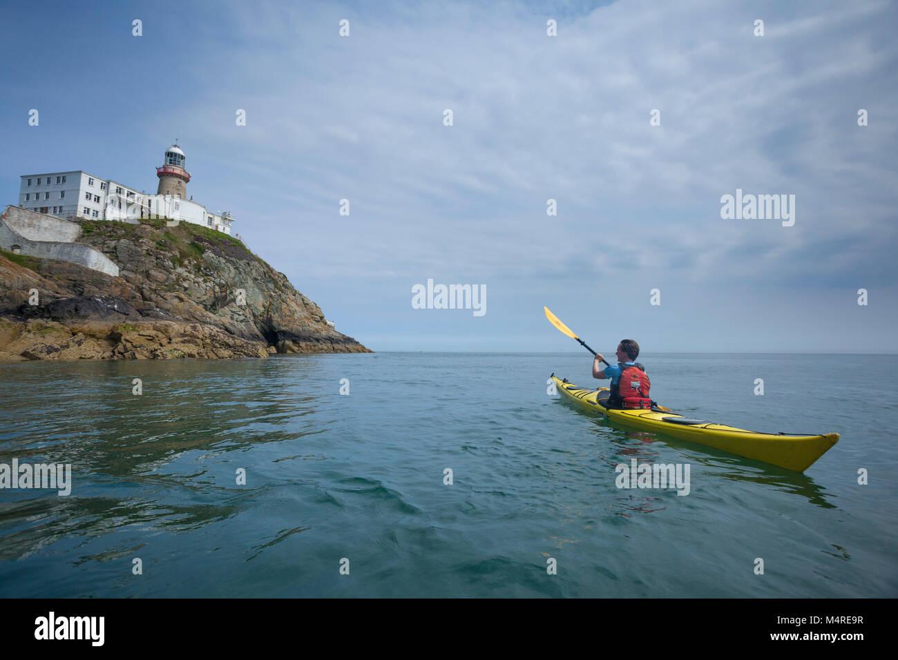 Sea kayaker beneath Baily Lighthouse, Howth Head, County Dublin, Ireland. - Stock Image