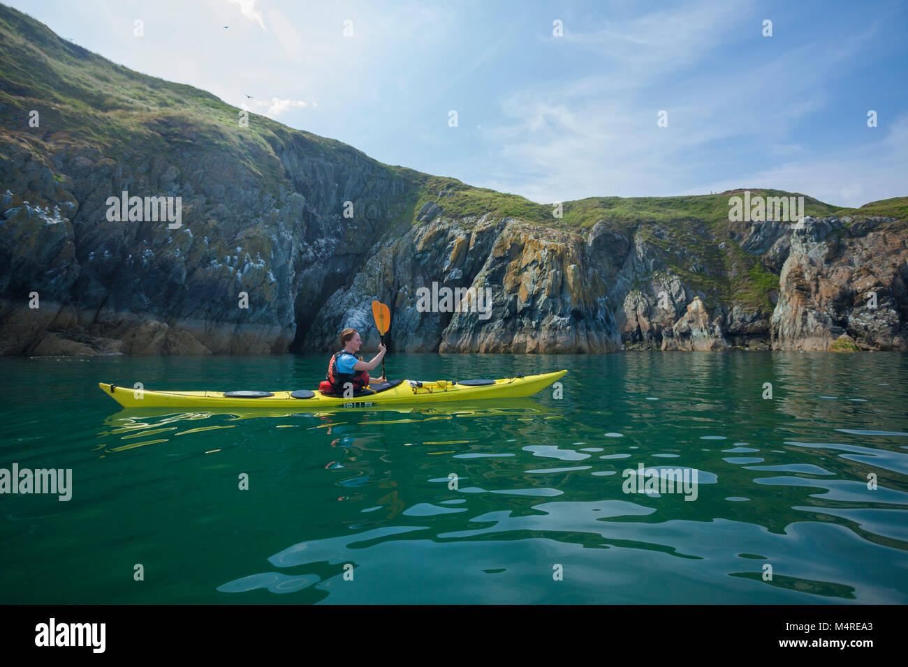 Sea kayaker beneath the cliffs of Howth Head, County Dublin, Ireland. - Stock Image