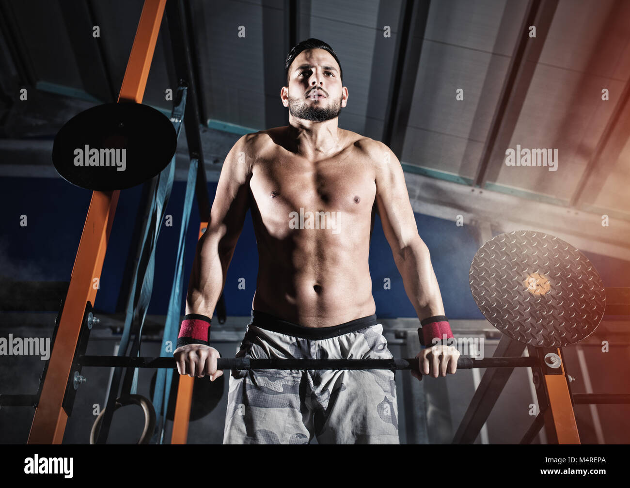 Athletic man works out at the gym with the bar - Stock Image