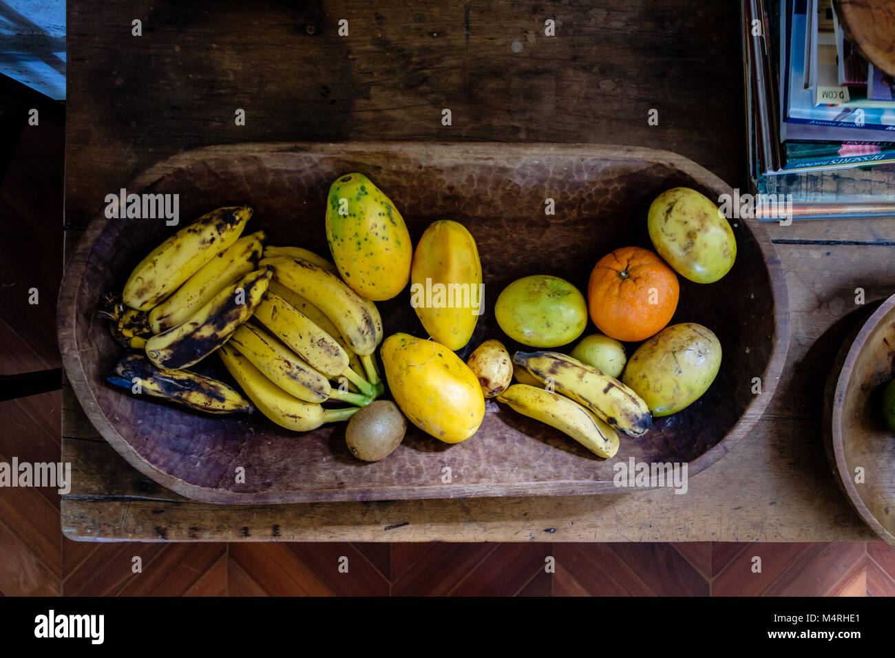 various fruits on a wooden platter with incoming sunlight. There are bananas, oranges, papaya - Stock Image