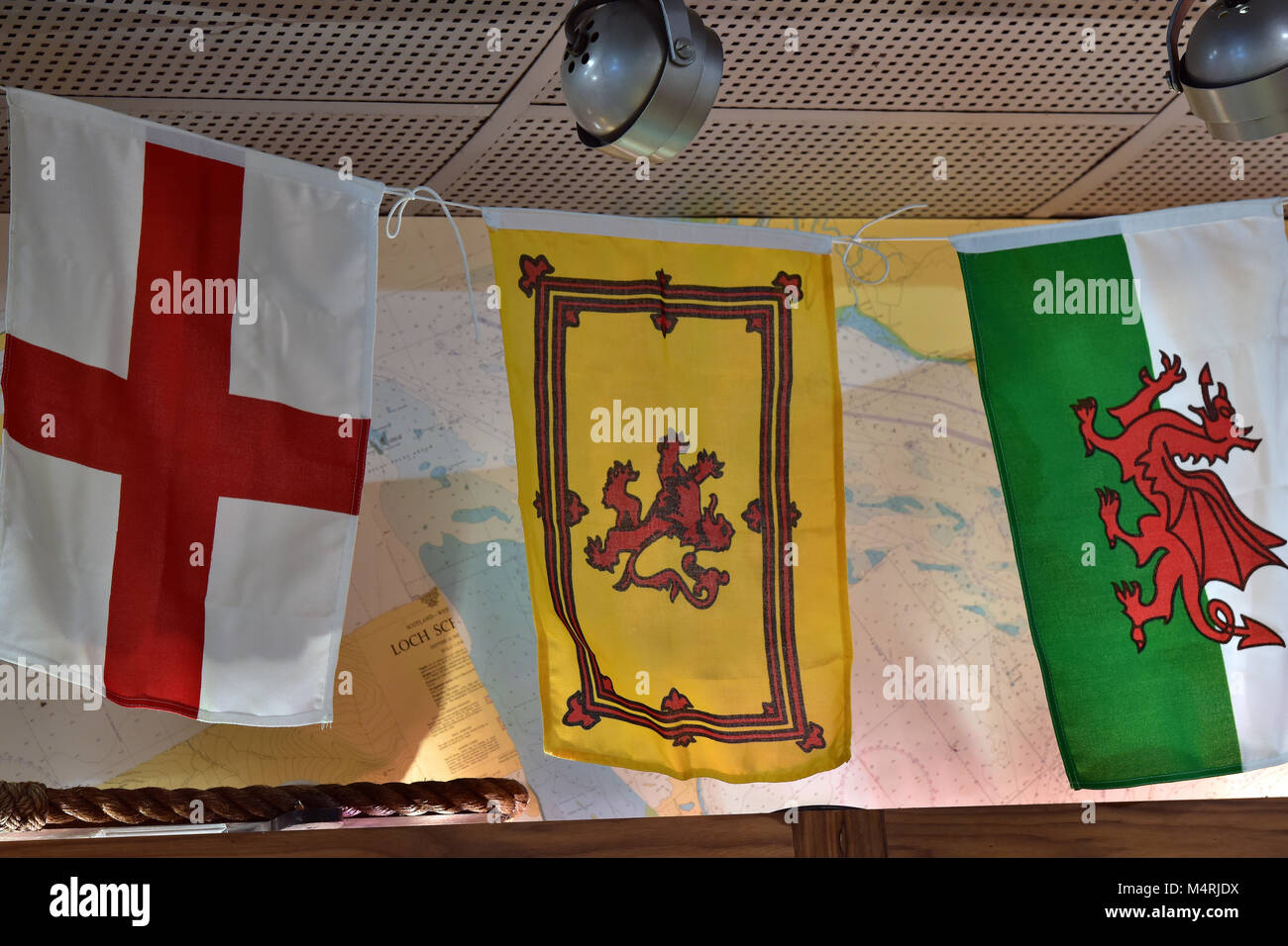 The flags or banners national identity of England Scotland and wales three nations Great Britain hanging together - Stock Image