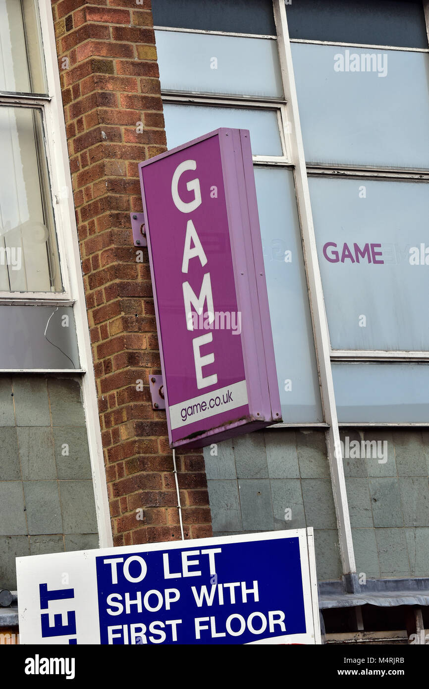 the game store high street retailer of computer games and accessories with a to let sign next to it and underneath, - Stock Image