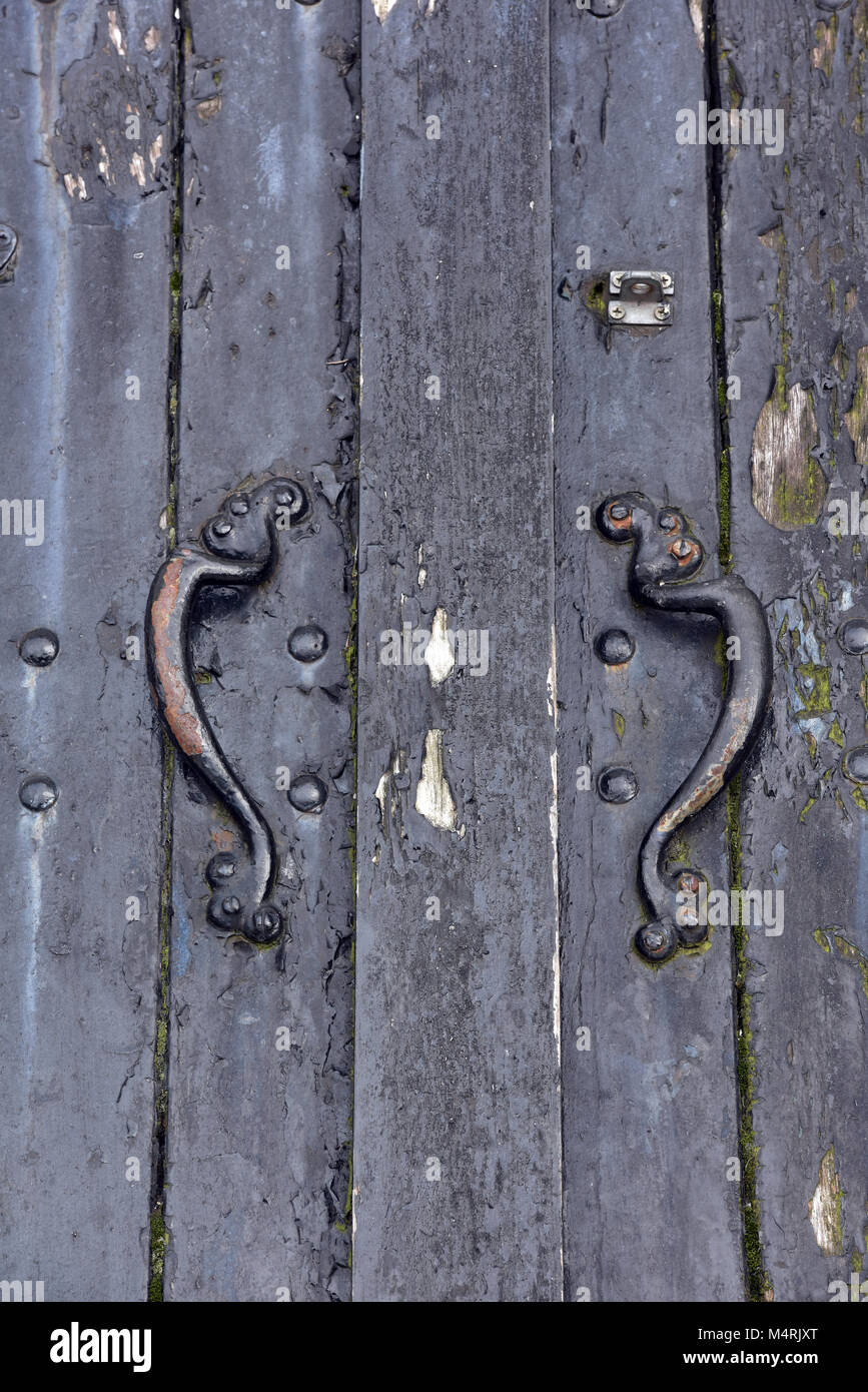 the doors to a beer cellar at a public house for delivering beer with the draymen. old iron handles on antique wooden - Stock Image