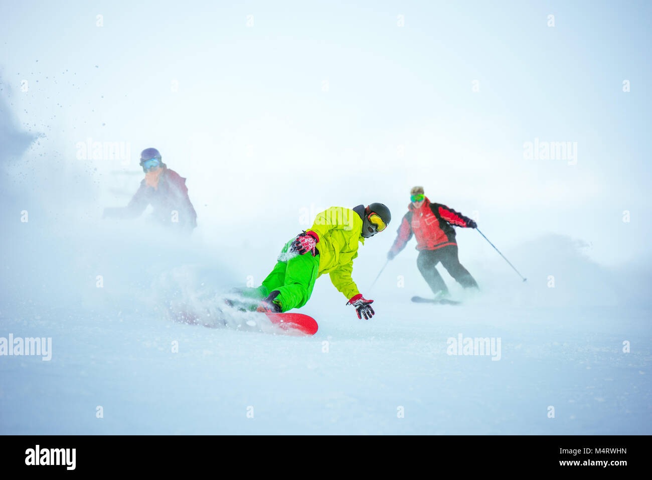 Ski downhill concept with group of snowboarders - Stock Image