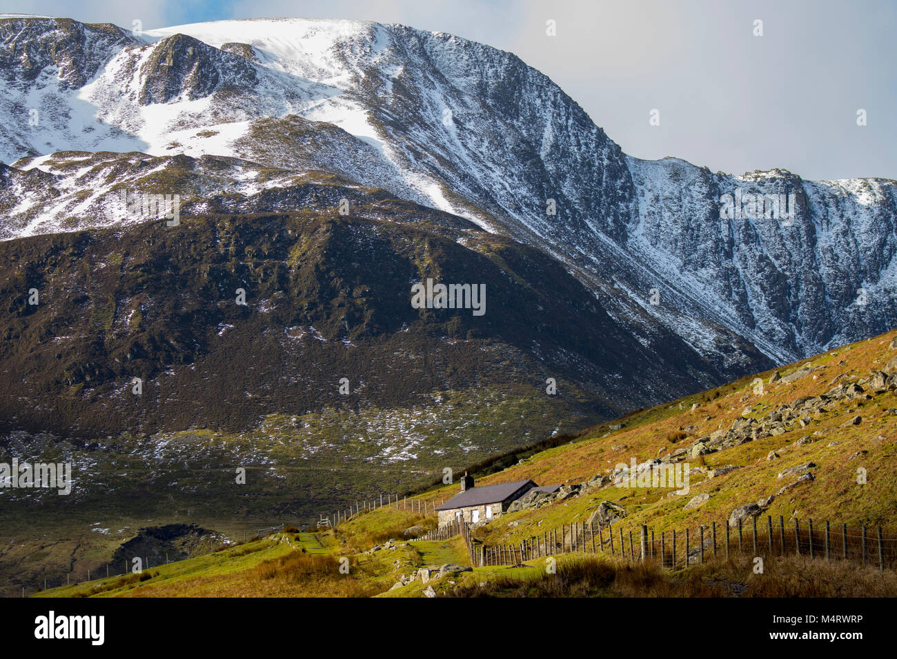 Wild welsh landscape in winter with sun shining over a old farmhouse in the Cwm Eigiau or Eigau Valley with snow - Stock Image
