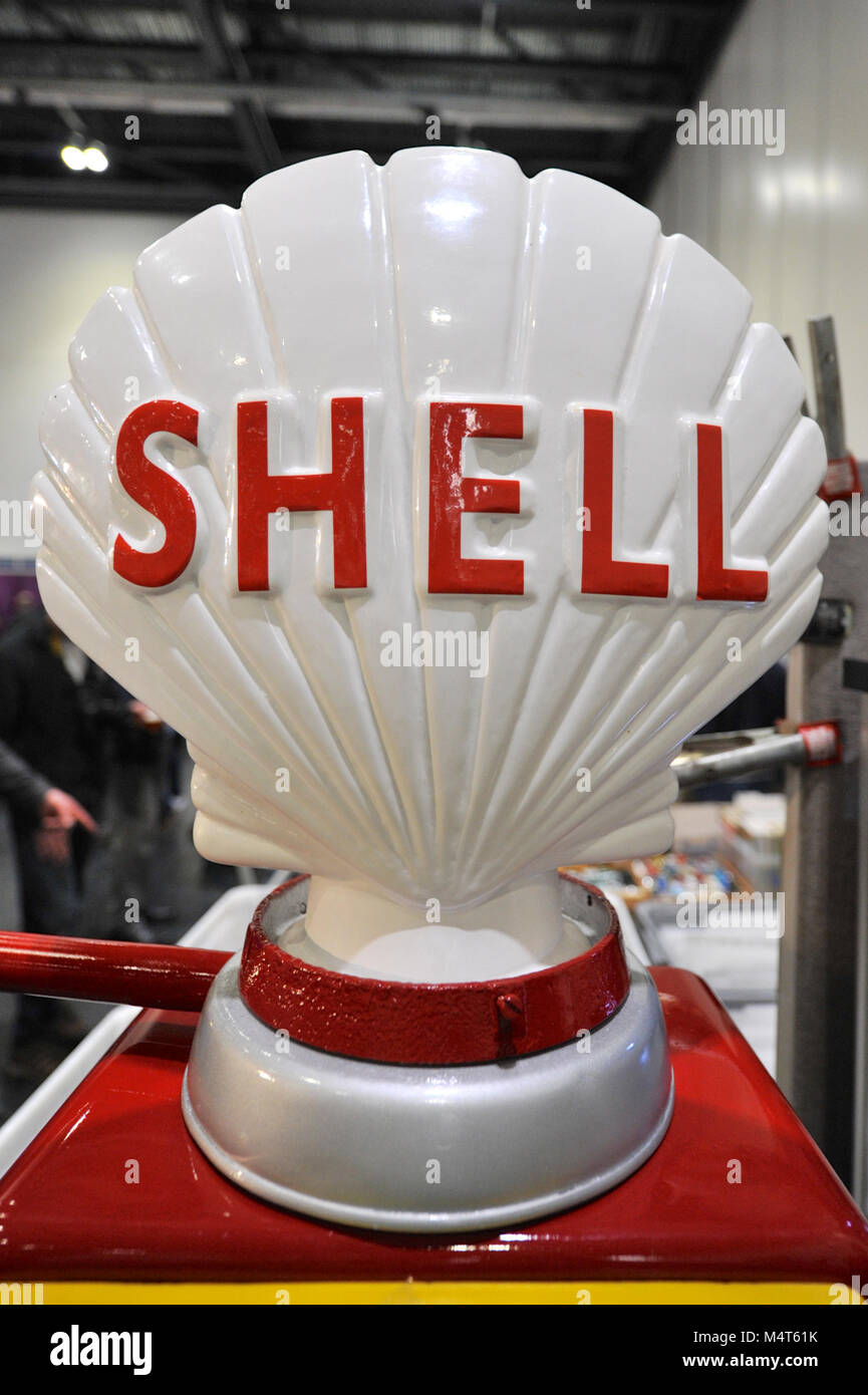 An Shell sign on top of a vintage petrol pump on display at the London Classic Car Show which is taking place at - Stock Image
