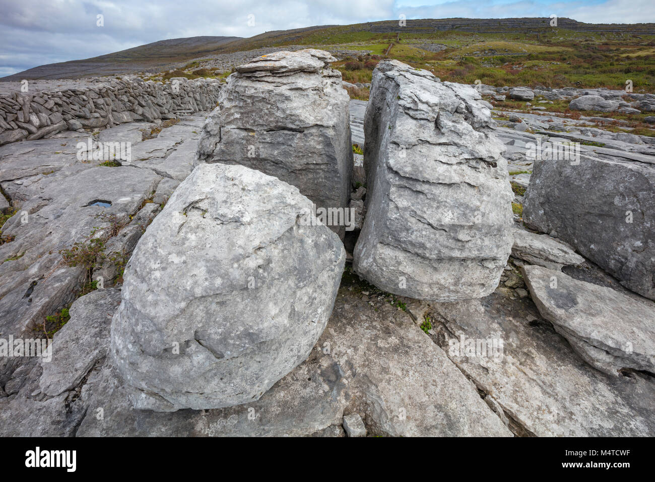 Limestone pavement and boulders in The Burren, County Clare, Ireland. - Stock Image