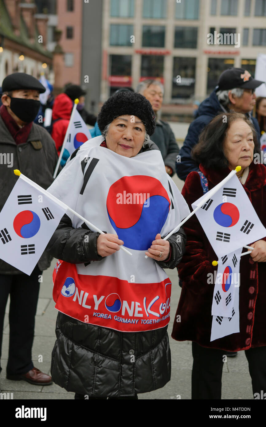 Frankfurt, Germany. 17th Feb, 2018. An older woman wears a cape with the Korean flag on it and holds two Korean Stock Photo