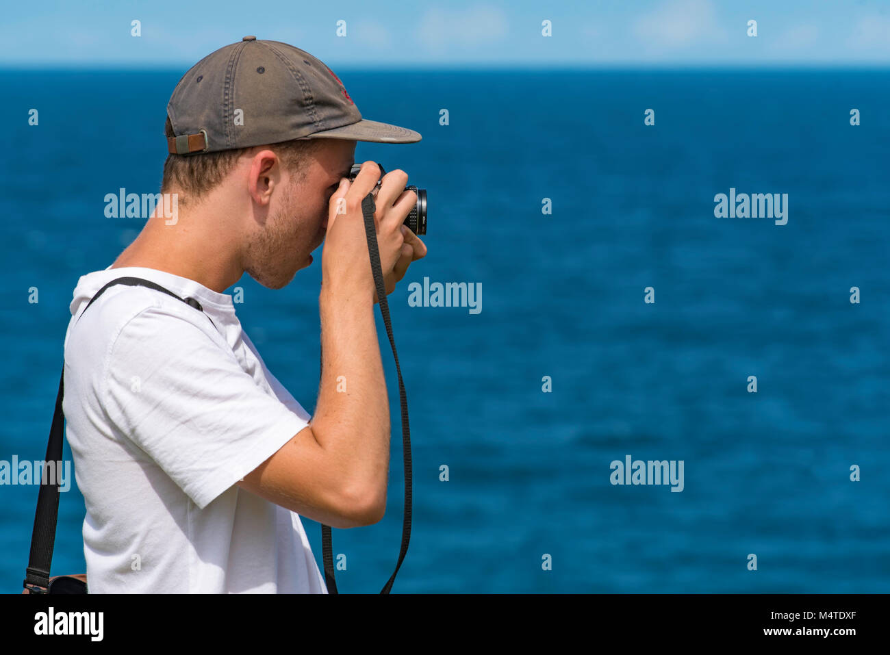 A young man taking photos near the ocean with an analogue SLR camera Stock Photo