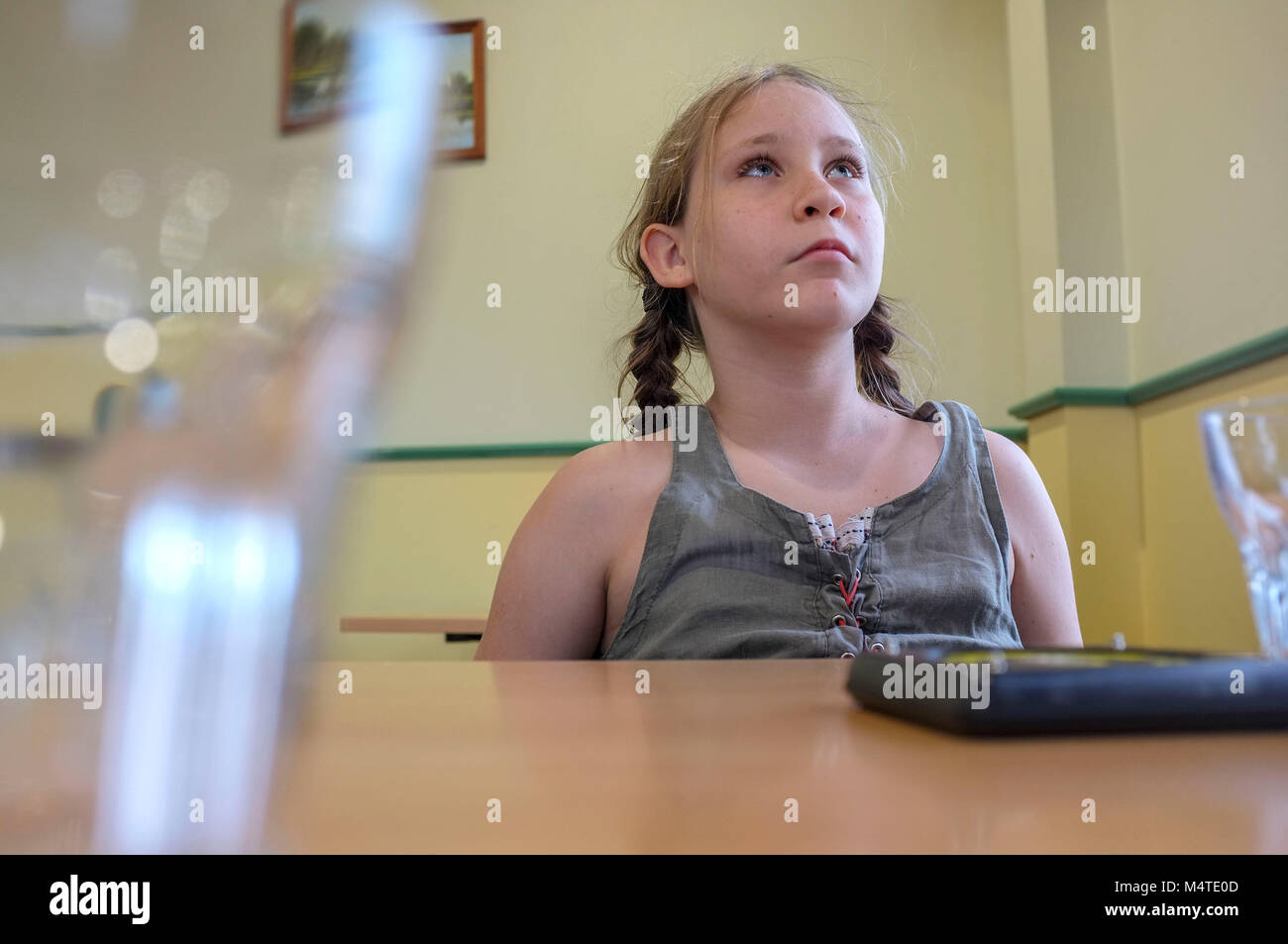 Pre-teen girl looking up and waiting for a meal in a pub. - Stock Image