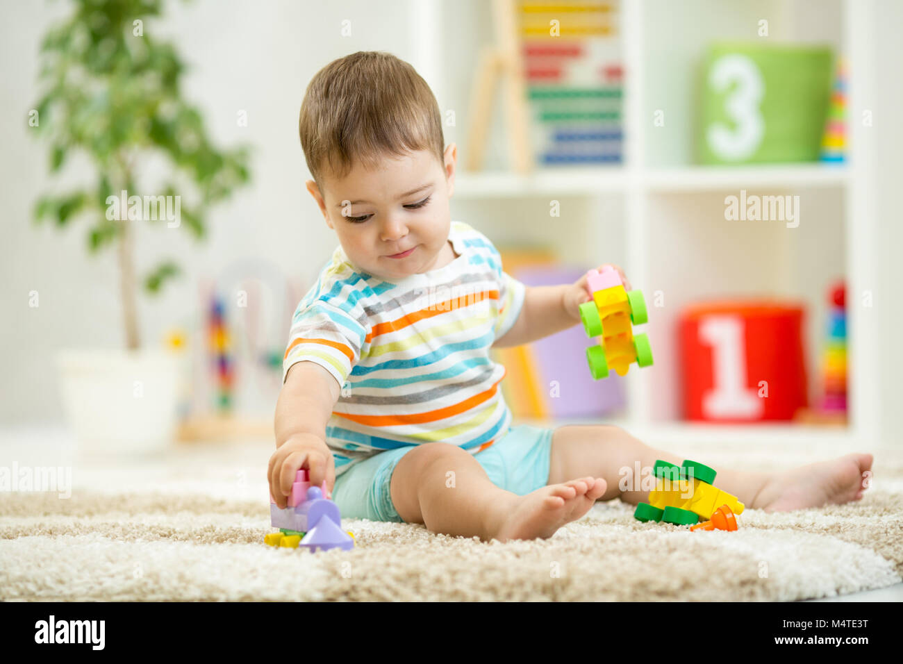 Happy baby playing with colorful plastic bricks on the floor. Toddler having fun and building a train out of constructor - Stock Image