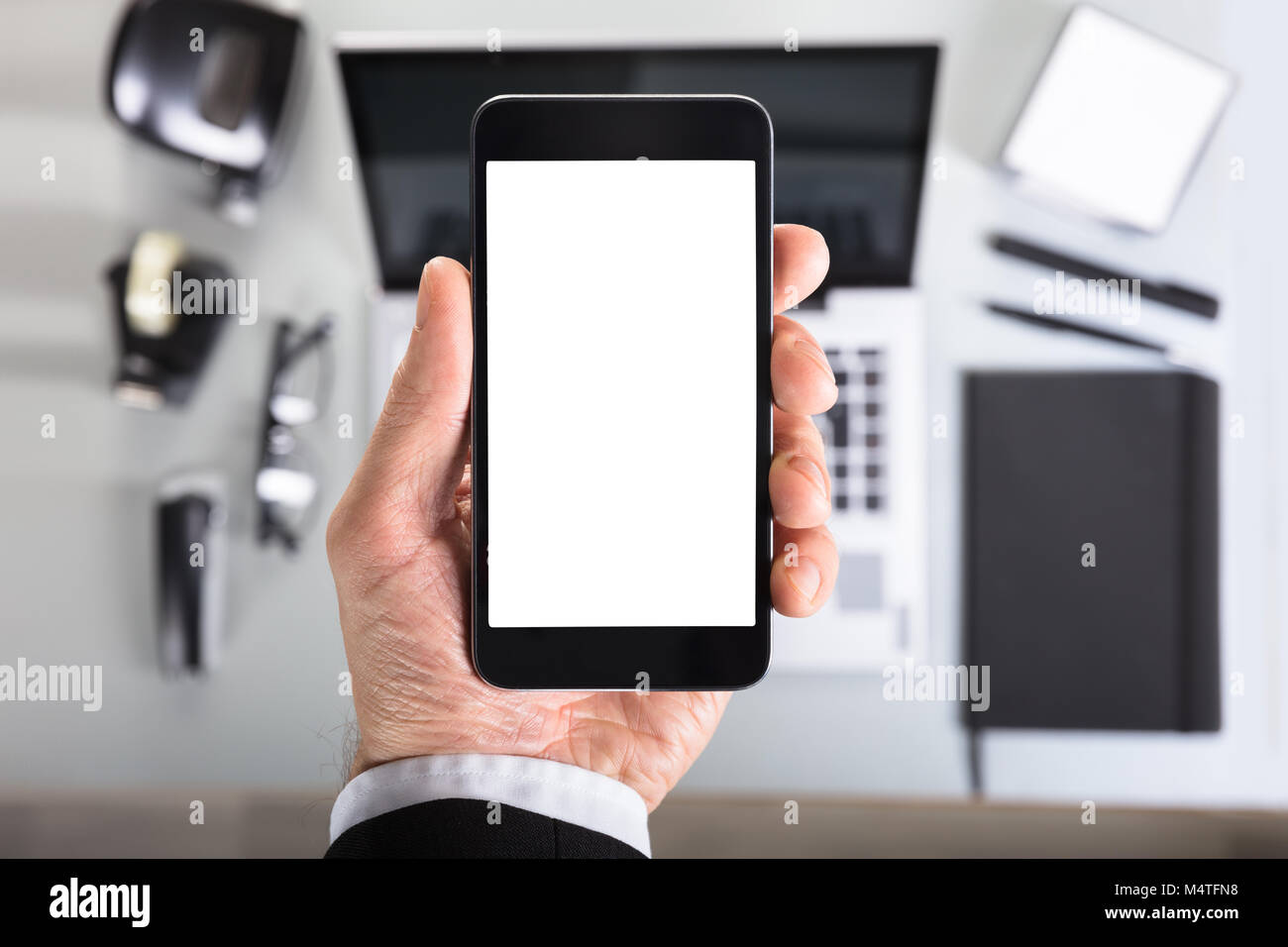 Close-up Of A Businessperson's Hand Showing Smart Phone Blank Screen In Office Stock Photo