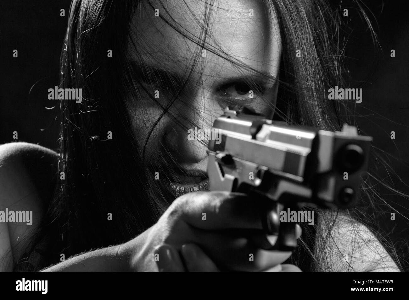 angry young woman with gun aiming on red background, monochrome - Stock Image