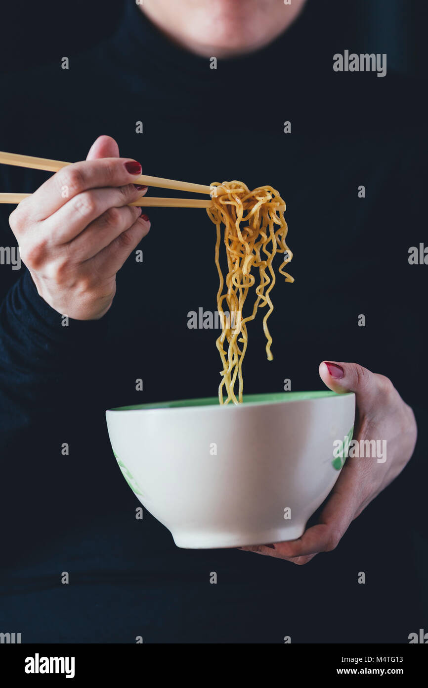 Woman holds a bowl of noodles with chopsticks - Stock Image