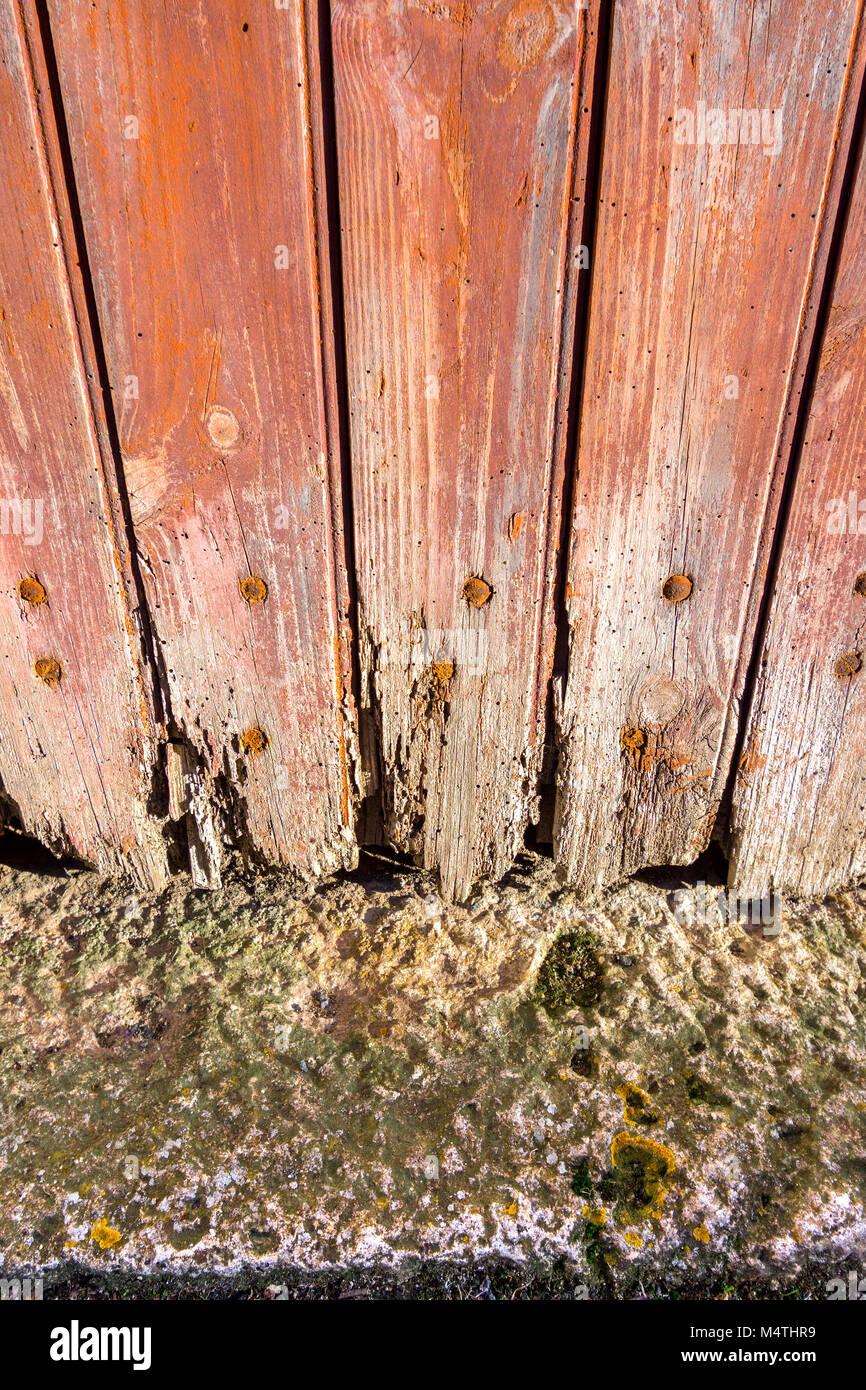 Rotten boards at foot of door. - Stock Image