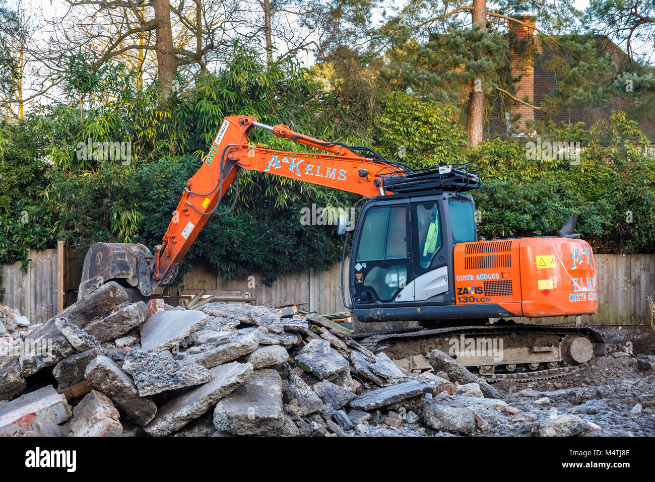 Construction site with orange heavy plant tracked mechanical excavator: remains of the demolition of a residential - Stock Image