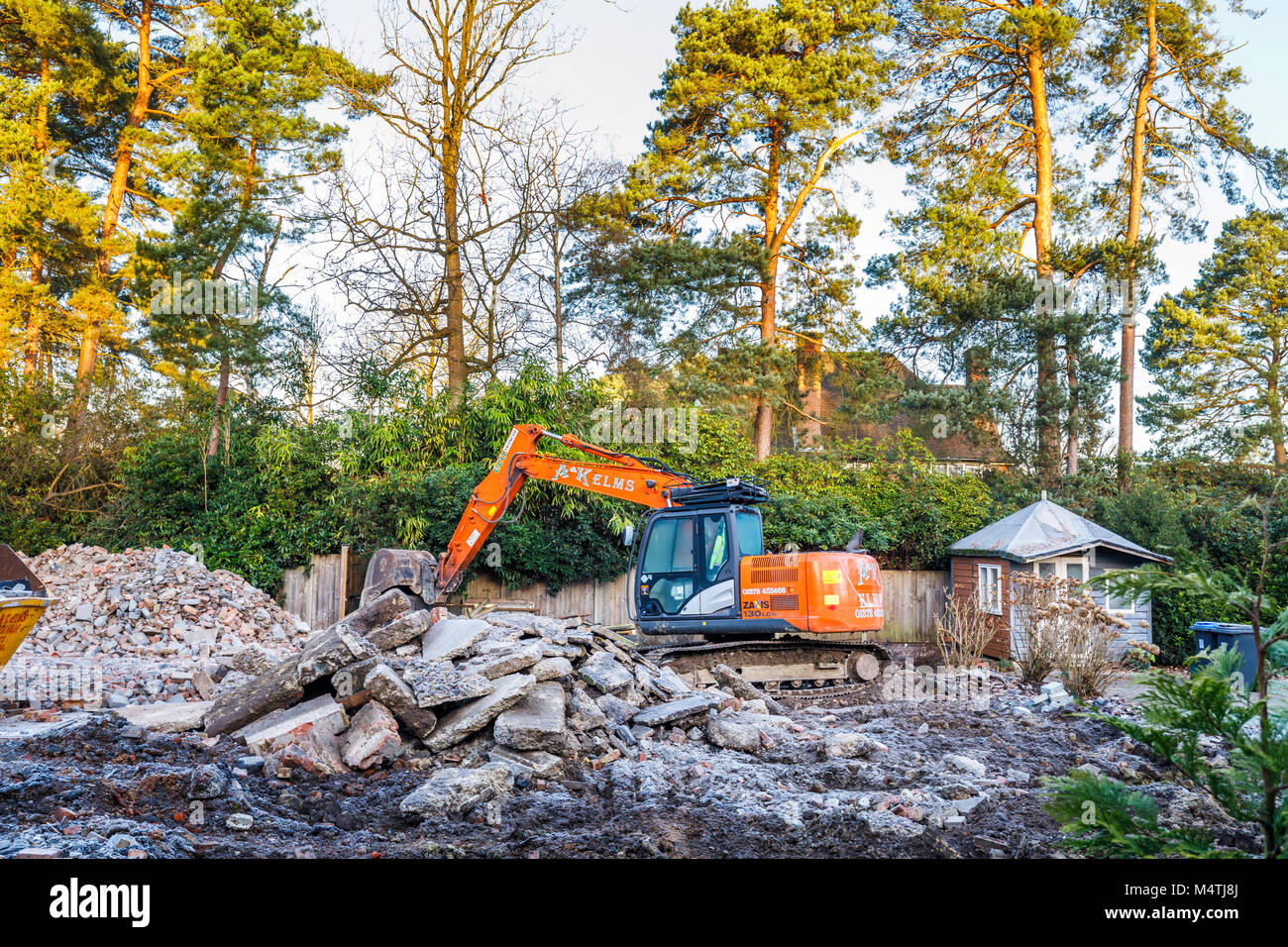 Construction site with orange heavy plant tracked mechanical excavator and skip: remains of demolition of a residential Stock Photo
