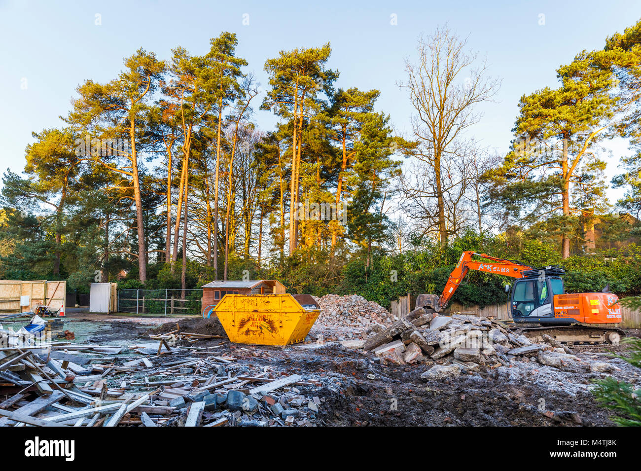 Construction site with orange heavy plant tracked mechanical excavator and skip: remains of demolition of a residential - Stock Image