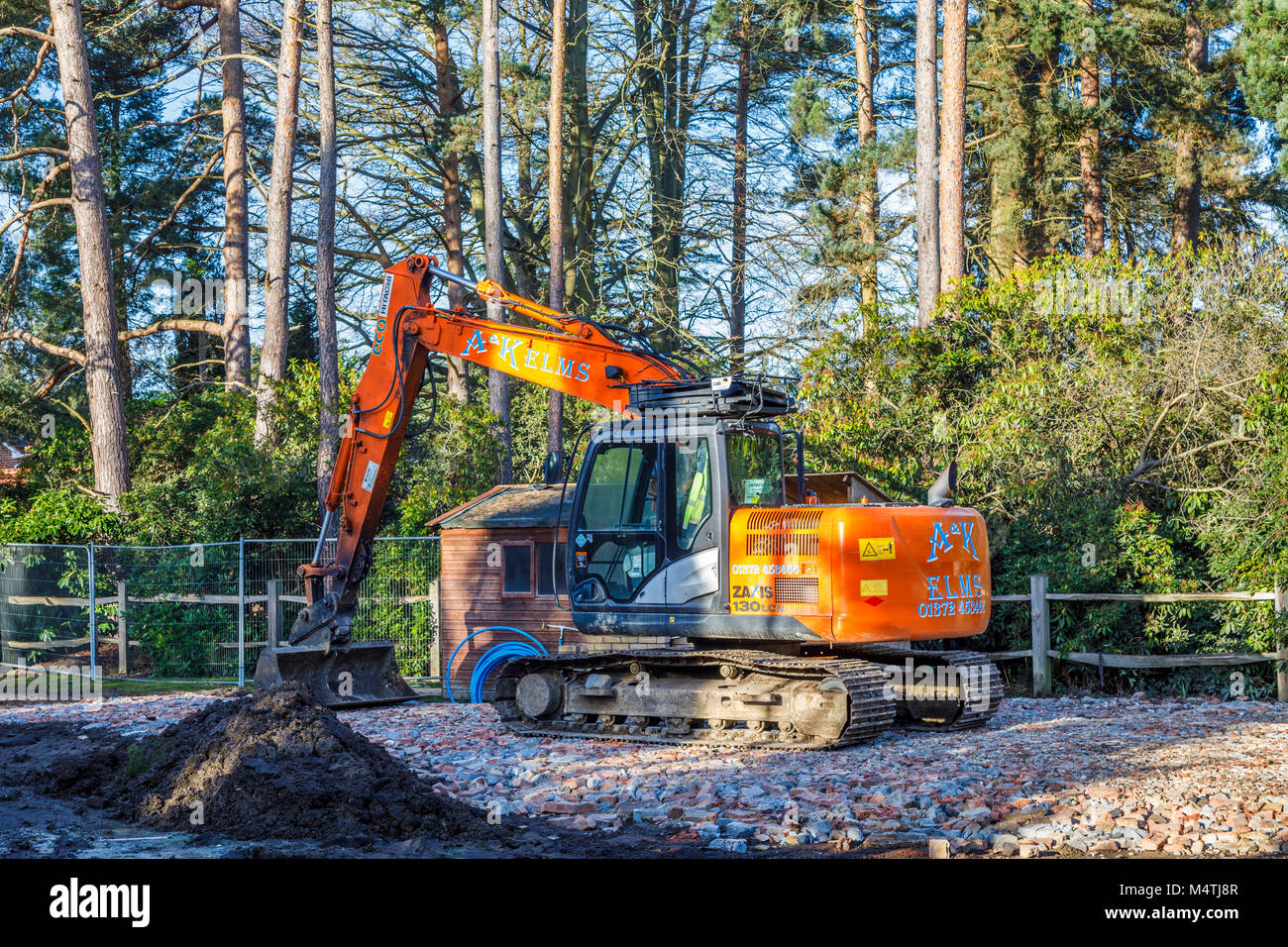 Large orange mechanical digger standing on a platform of hard core brick rubble on a cleared demolition site preparing - Stock Image