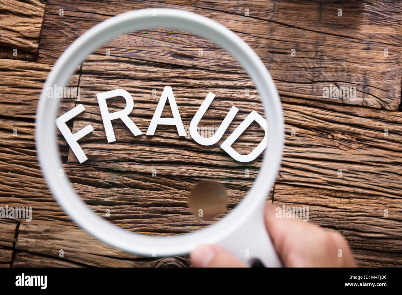 A Person Looking At White Fraud Text Through Magnifying Glass - Stock Image