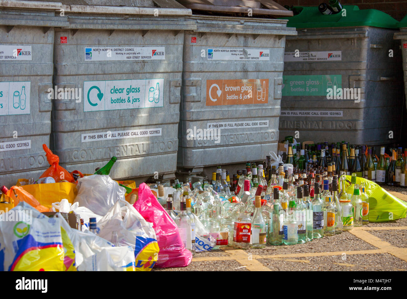Overflowing glass bottle banks. A local authority glass recycling point is overflowing with glass & waste left - Stock Image