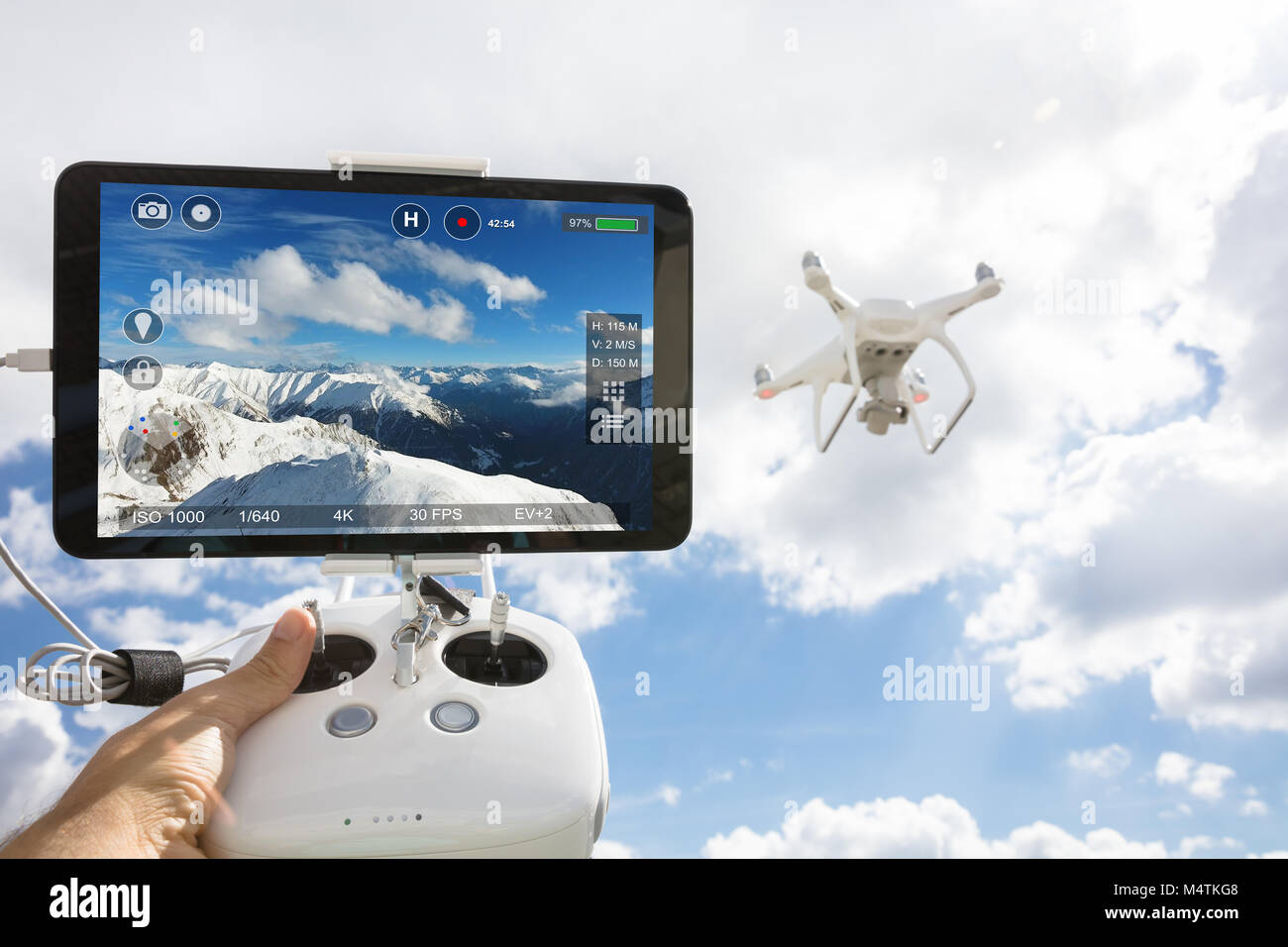 Cropped image of hand controlling drone filming snowcapped mountainsagainst cloudy sky - Stock Image