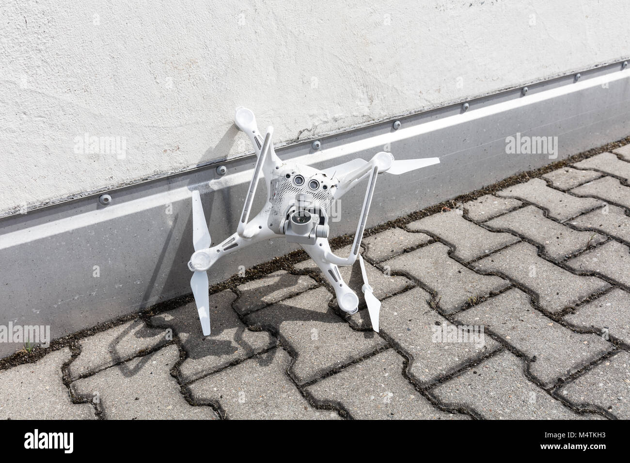 High angle view of broken drone on footpath - Stock Image