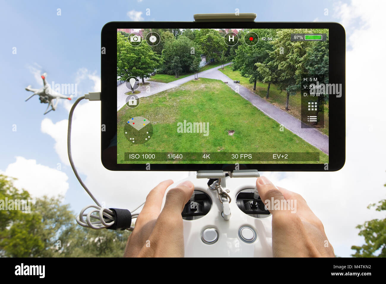 Cropped image of hands controlling drone filming park seen on digital tablet - Stock Image