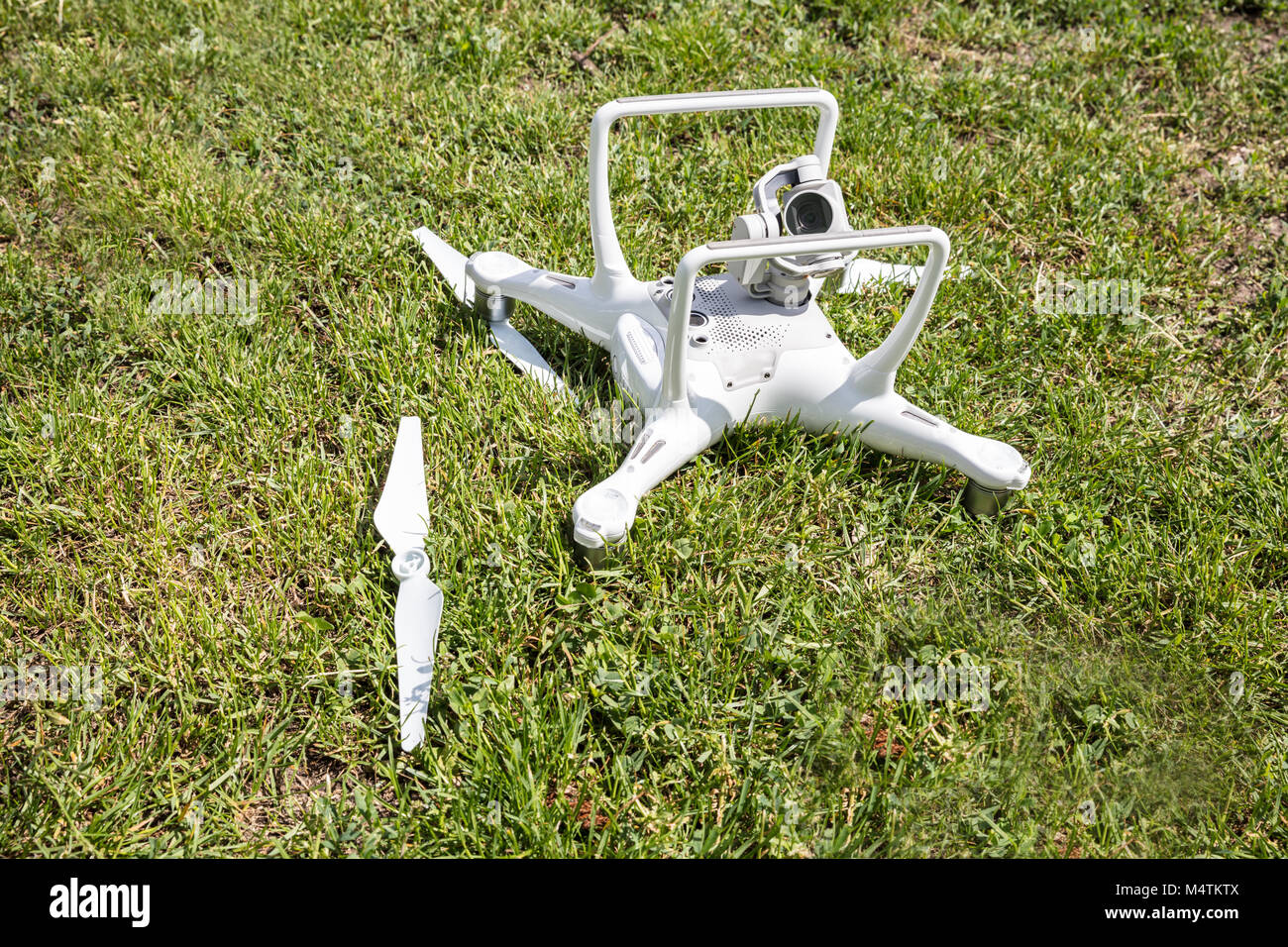 High angle view of broken drone on grassy field - Stock Image