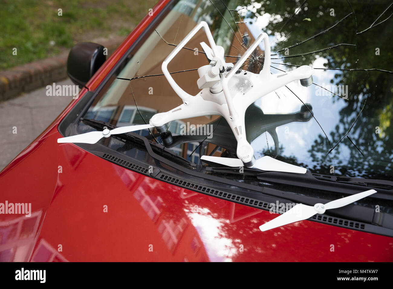 Closeup of damaged white drone on broken car windshield - Stock Image