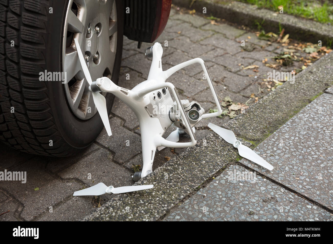High angle view of broken drone by car wheel on footpath - Stock Image