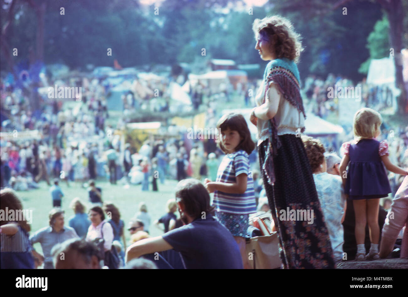 A beautiful hippie woman, man and children viewing the 1970s summer hippy music festival at Barsham Fair in Beccles, - Stock Image