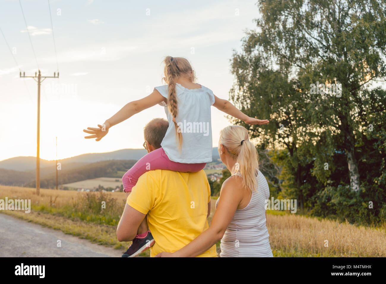 Family carrying child piggyback on summer walk - Stock Image