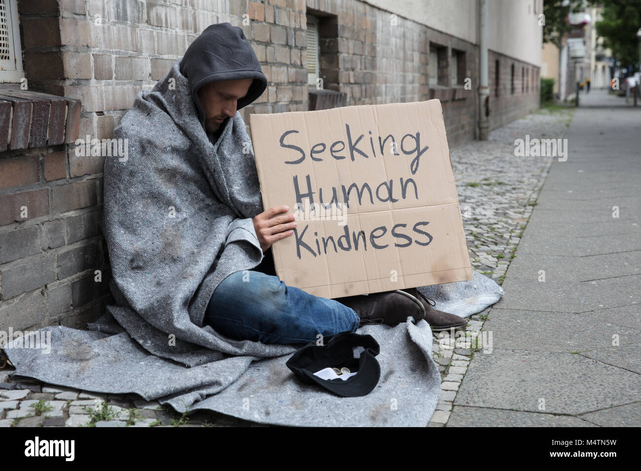 Male Beggar In Hood Showing Seeking Human Kindness Sign On Cardboard - Stock Image
