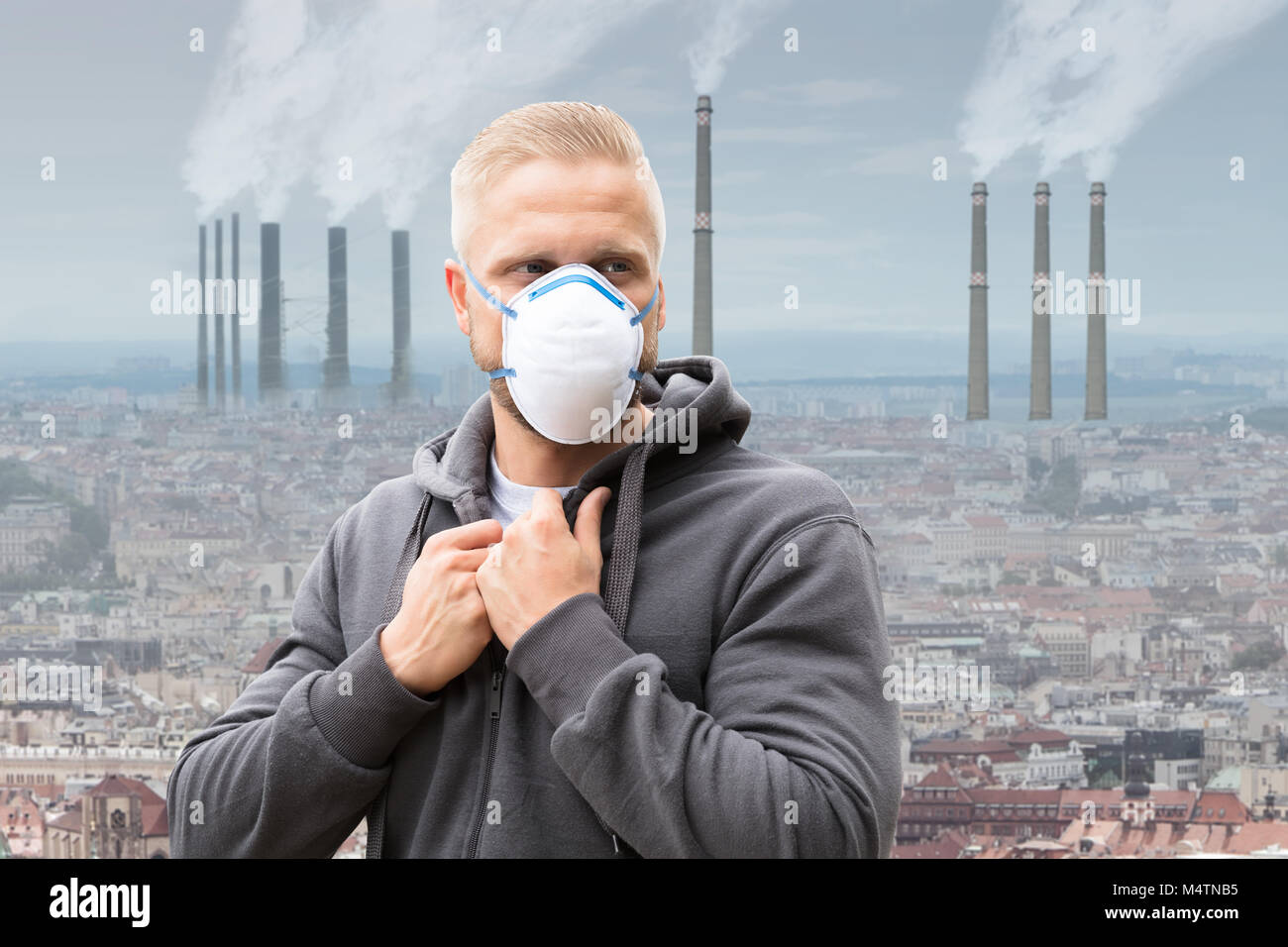 A Man Wearing Pollution Mask Against Smoke Emitting From Factory Chimneys - Stock Image