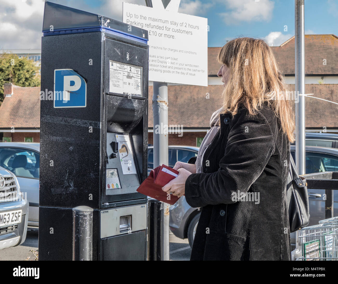 Middle aged woman standing in car park with purse open at ticket machine, in the Ruislip branch of Waitrose supermarket, - Stock Image