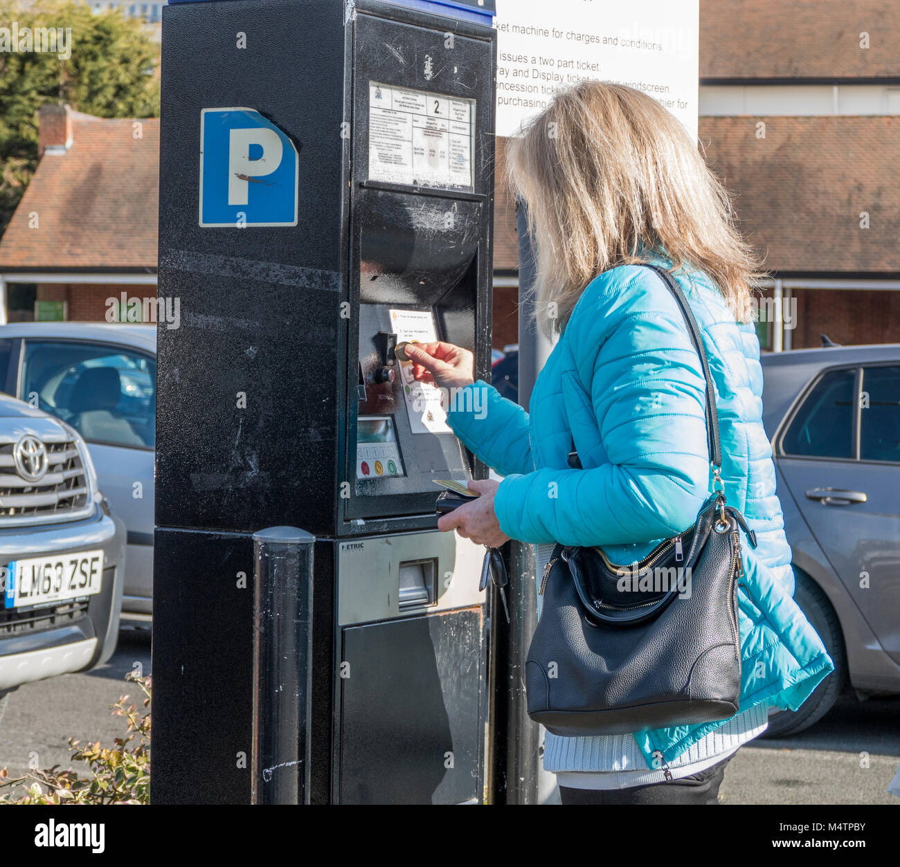 Middle aged woman standing in car park inserting coin at ticket machine in the Ruislip branch of Waitrose supermarket, - Stock Image