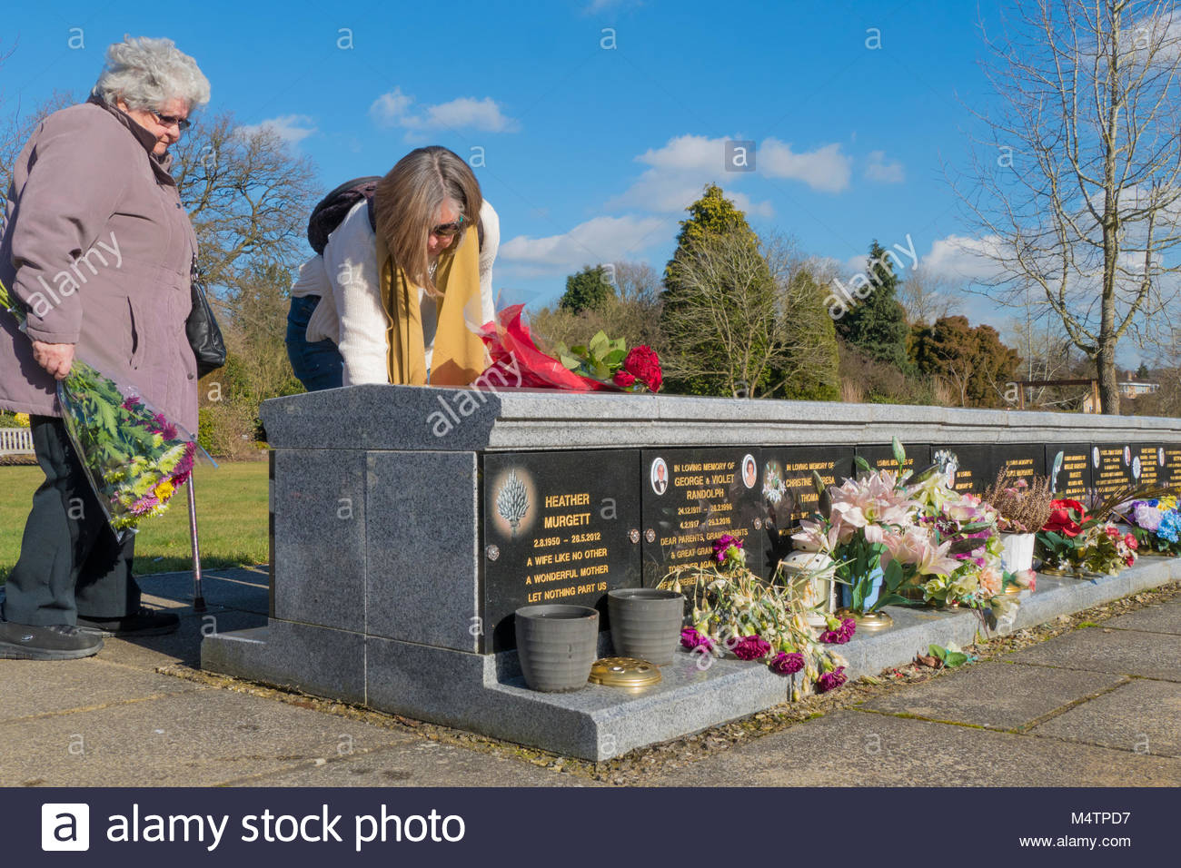 Old / elderly lady and her middle aged daughter, placing flowers for their loved one at Breakspear Crematorium, - Stock Image