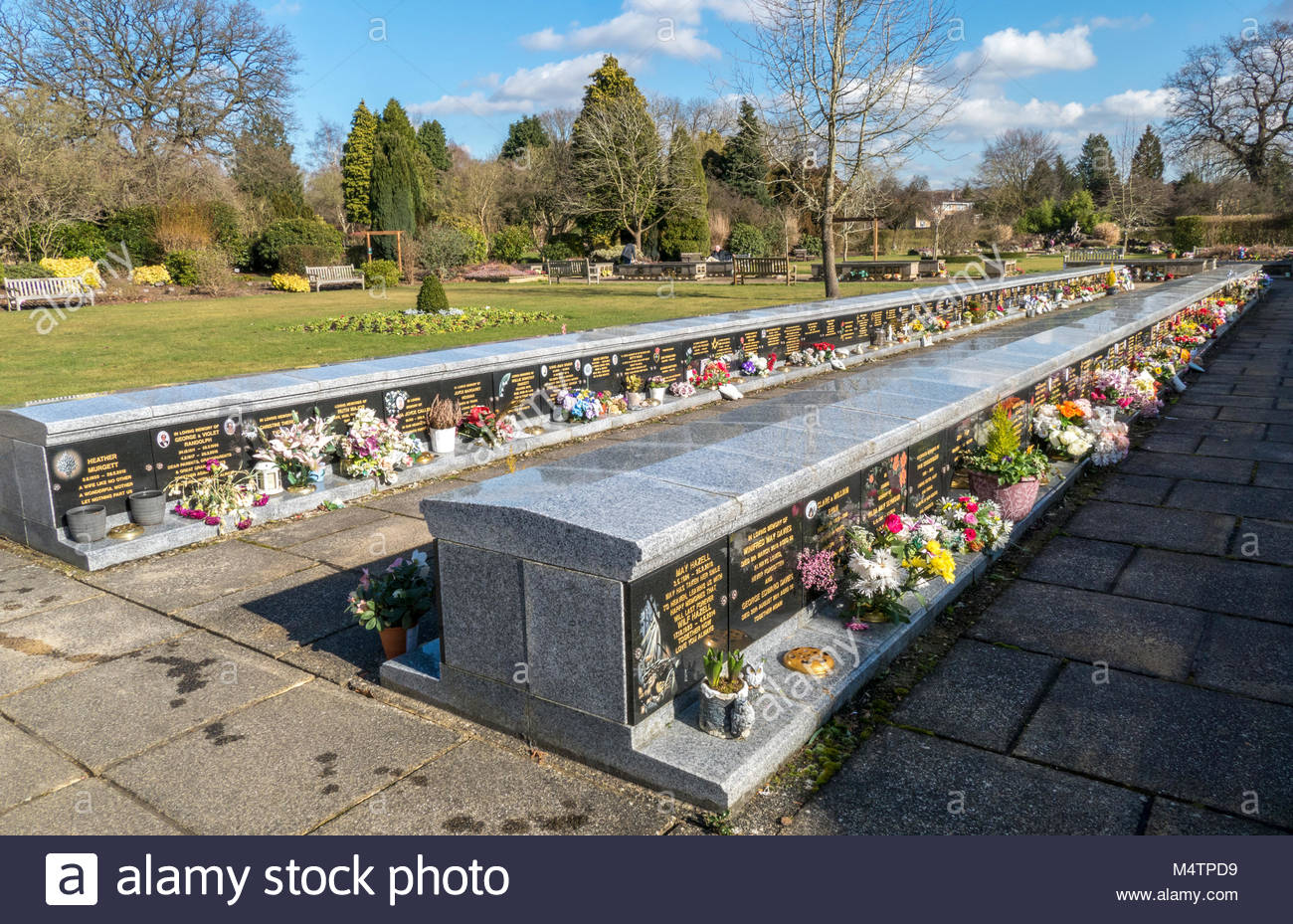 Flower displays at rows of granite memorials, at a peaceful site with beautiful gardens. Breakspear Crematorium, - Stock Image