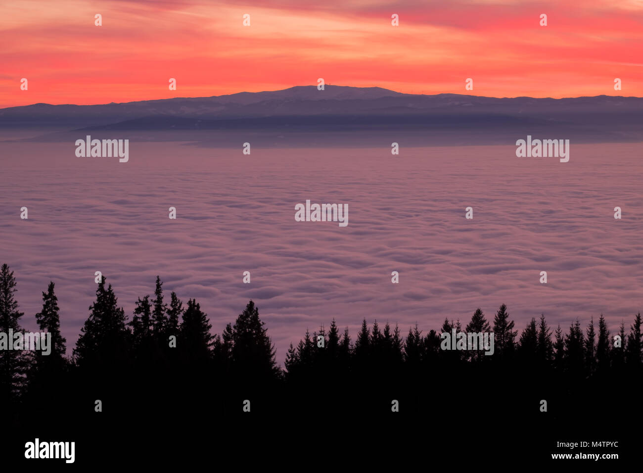 View from mountain Schoeckl over low stratus to mountain Koralpe with pinwheels and sunset Stock Photo