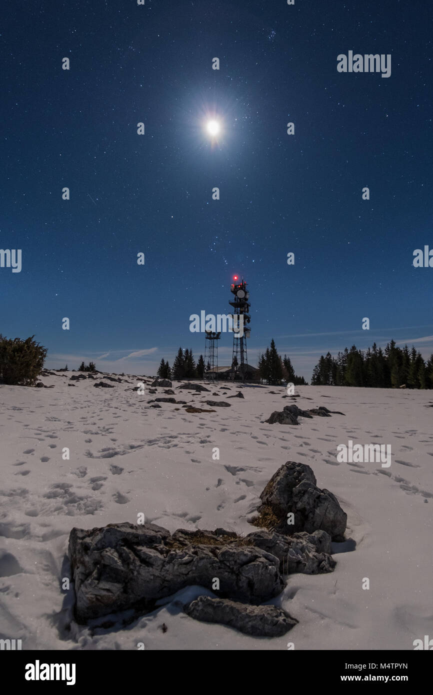 Transmitter station tower on snow covered mountain Schoeckl with moon and stars in the sky - Stock Image