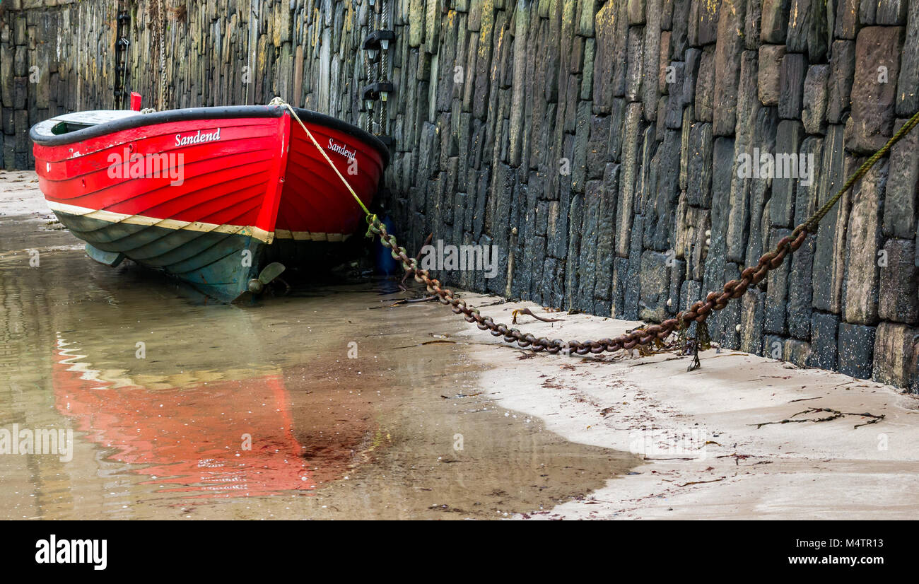 Close up of chained small red rowing boat at low tide from  Sandend, picturesque harbour, Portsoy, Aberdeenshire, - Stock Image