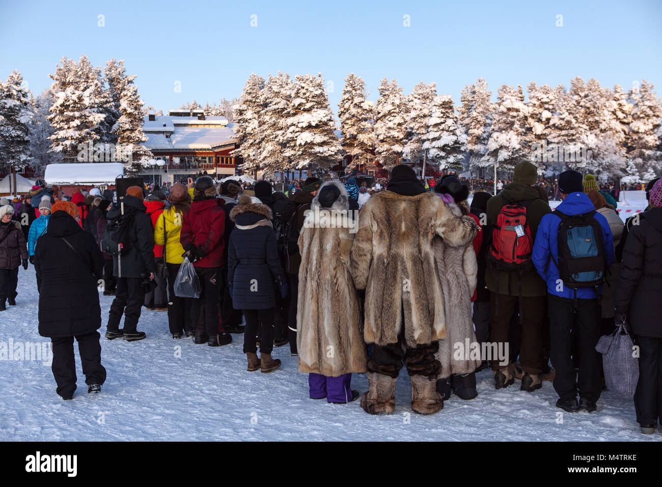 JOKKMOKK, SWEDEN ON FEBRUARY 03, 2018. View of well-dressed spectators from behind. Forest and buildings. Editorial - Stock Image