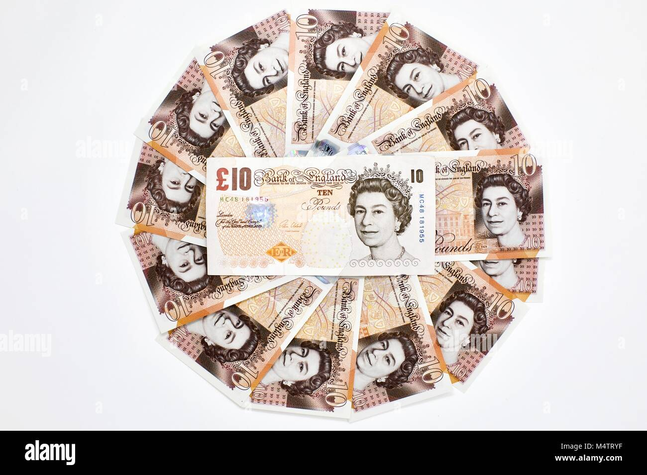 The old £10 banknote in the middle of a circle of the new-design polymer £10 banknotes on a white background - Stock Image