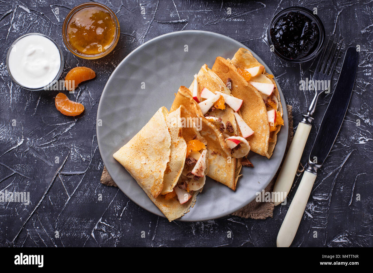 Pancakes crepes with different fruits and chocolate - Stock Image
