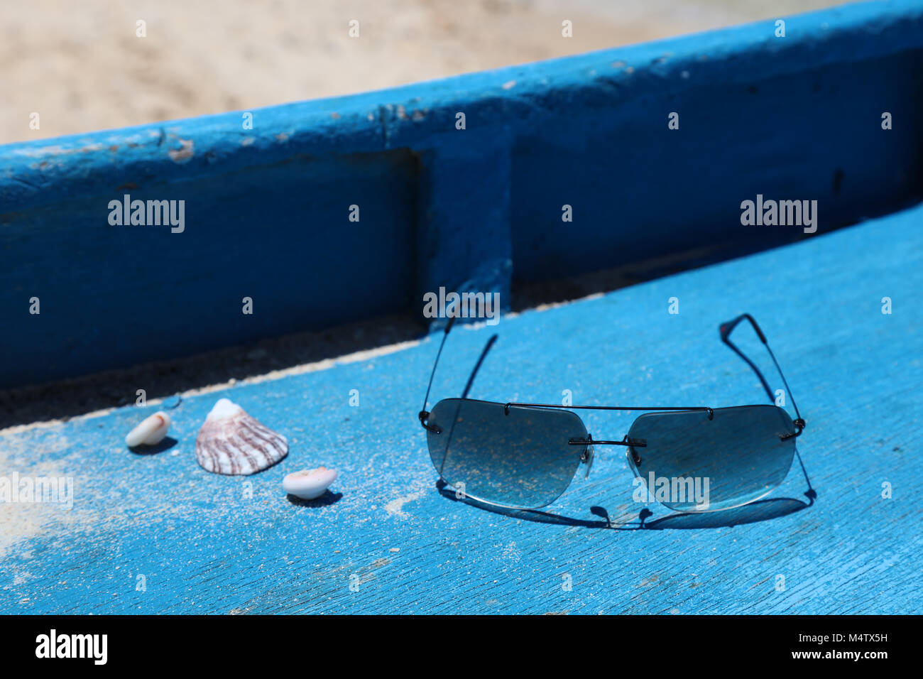 Shells and sun glasses on a boat deck, Boracay Island, Philippines. Concept of tropical vacation. - Stock Image