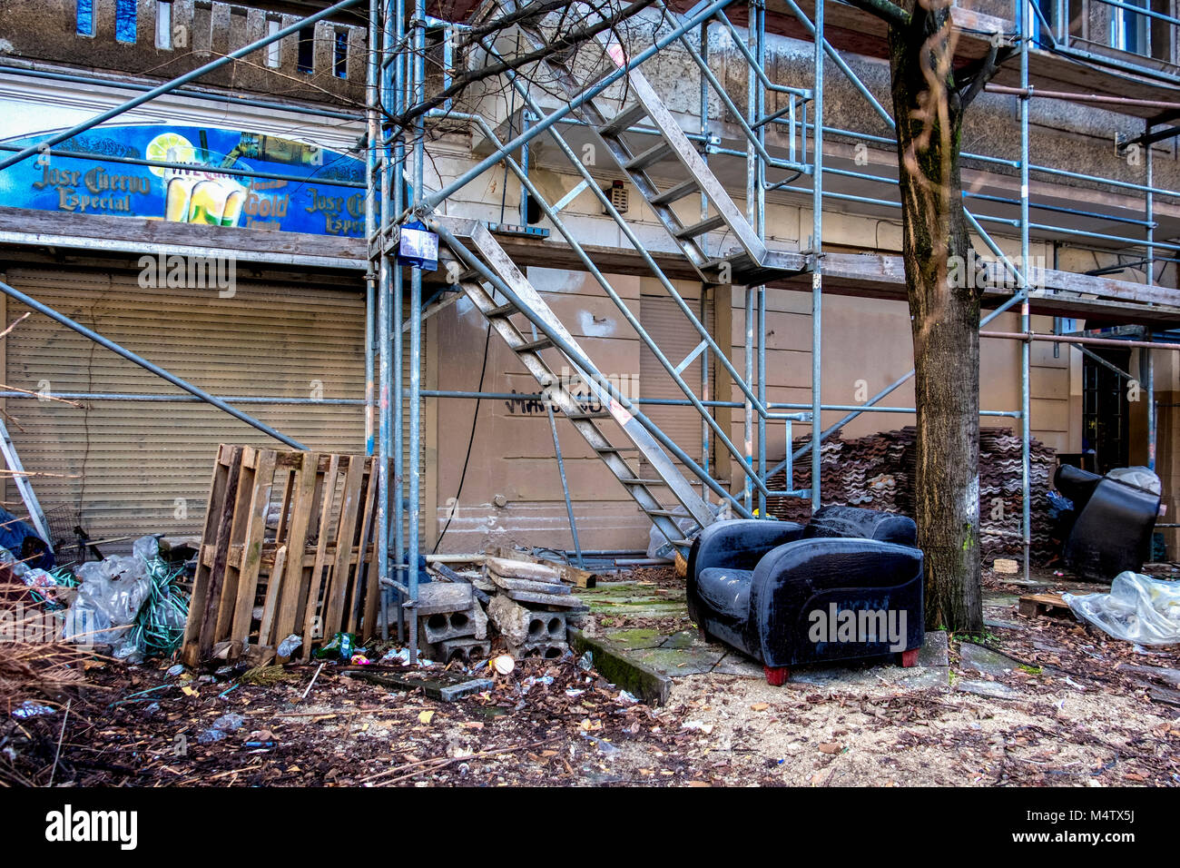 Berlin Prenzlauerberg,Street view .Contruction site with building materials,scaffolding and discardedd old sofa - Stock Image