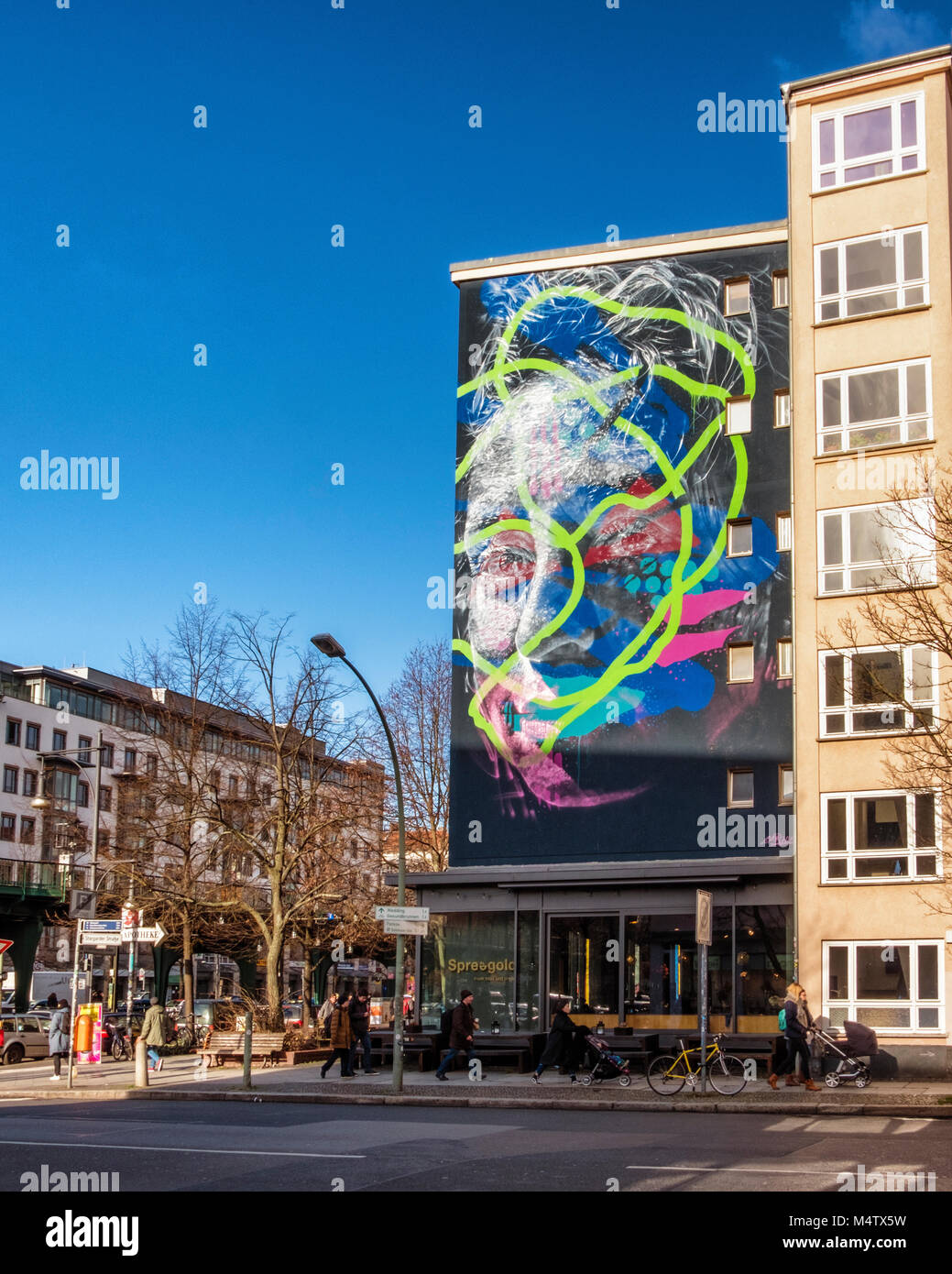 Berlin Prenzlauerberg,street view with shops, apartment buildings,people walking on pavement and colourful wall - Stock Image